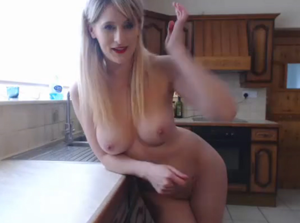 Mature blonde woman naked in the kitchen