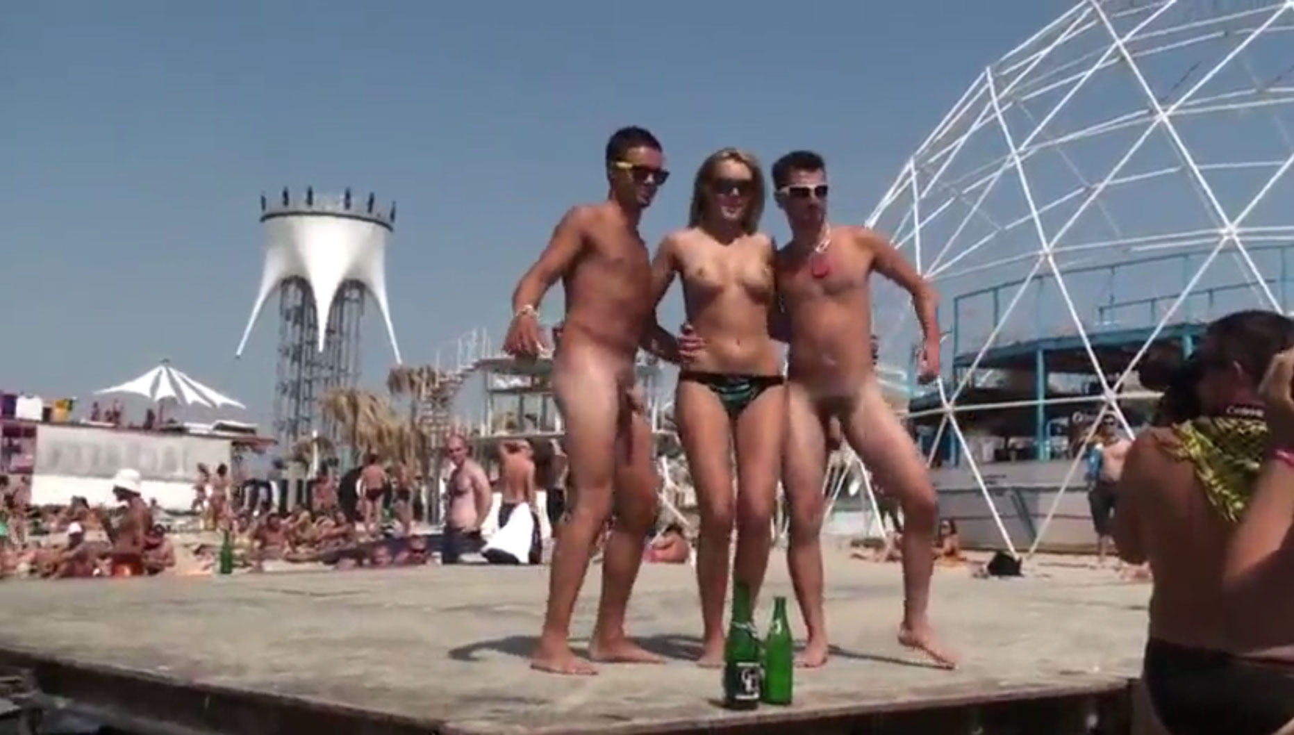 Topless girl dancing with 2 naked boys in festival