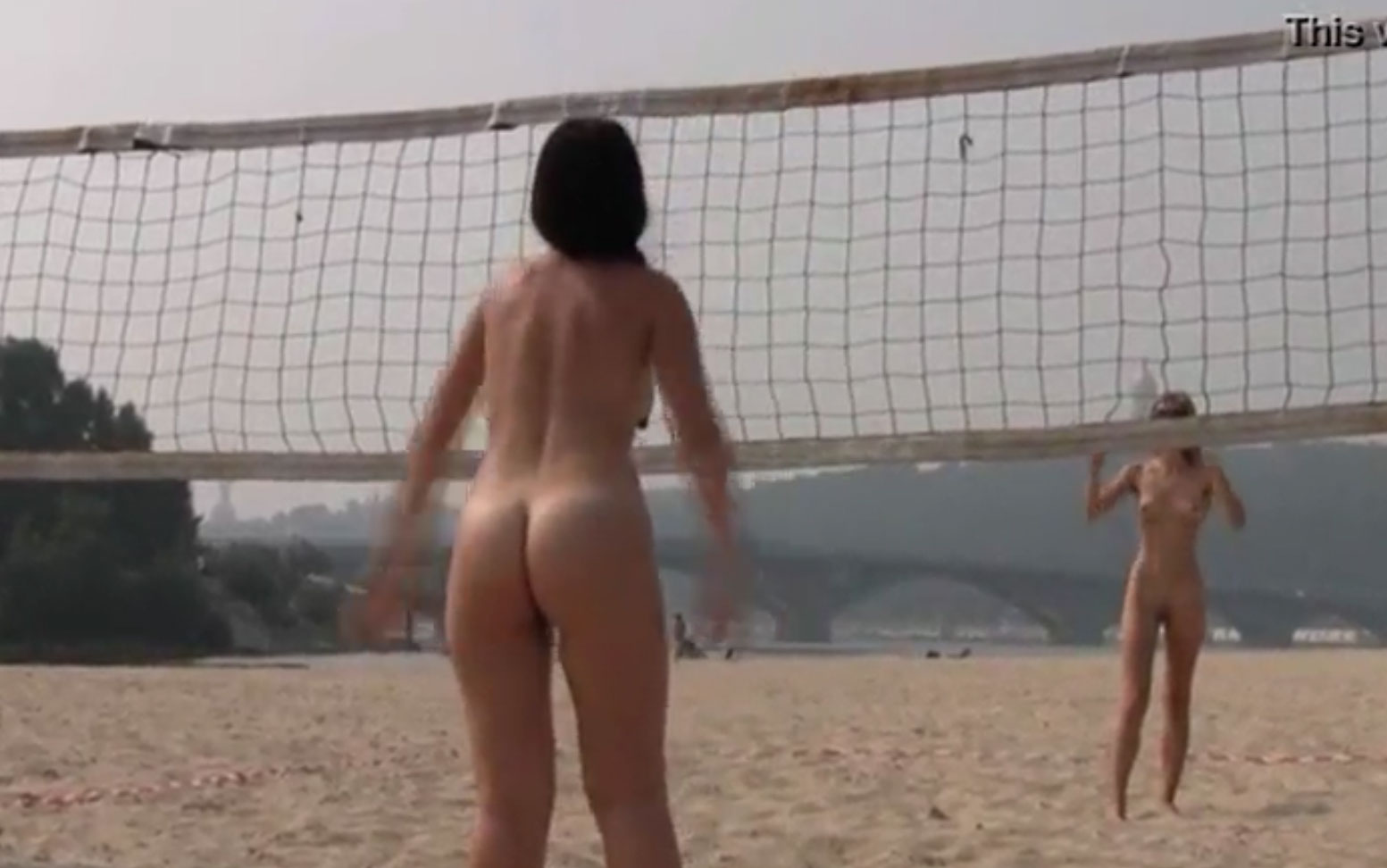 two naked teens playing volleyball on the beach