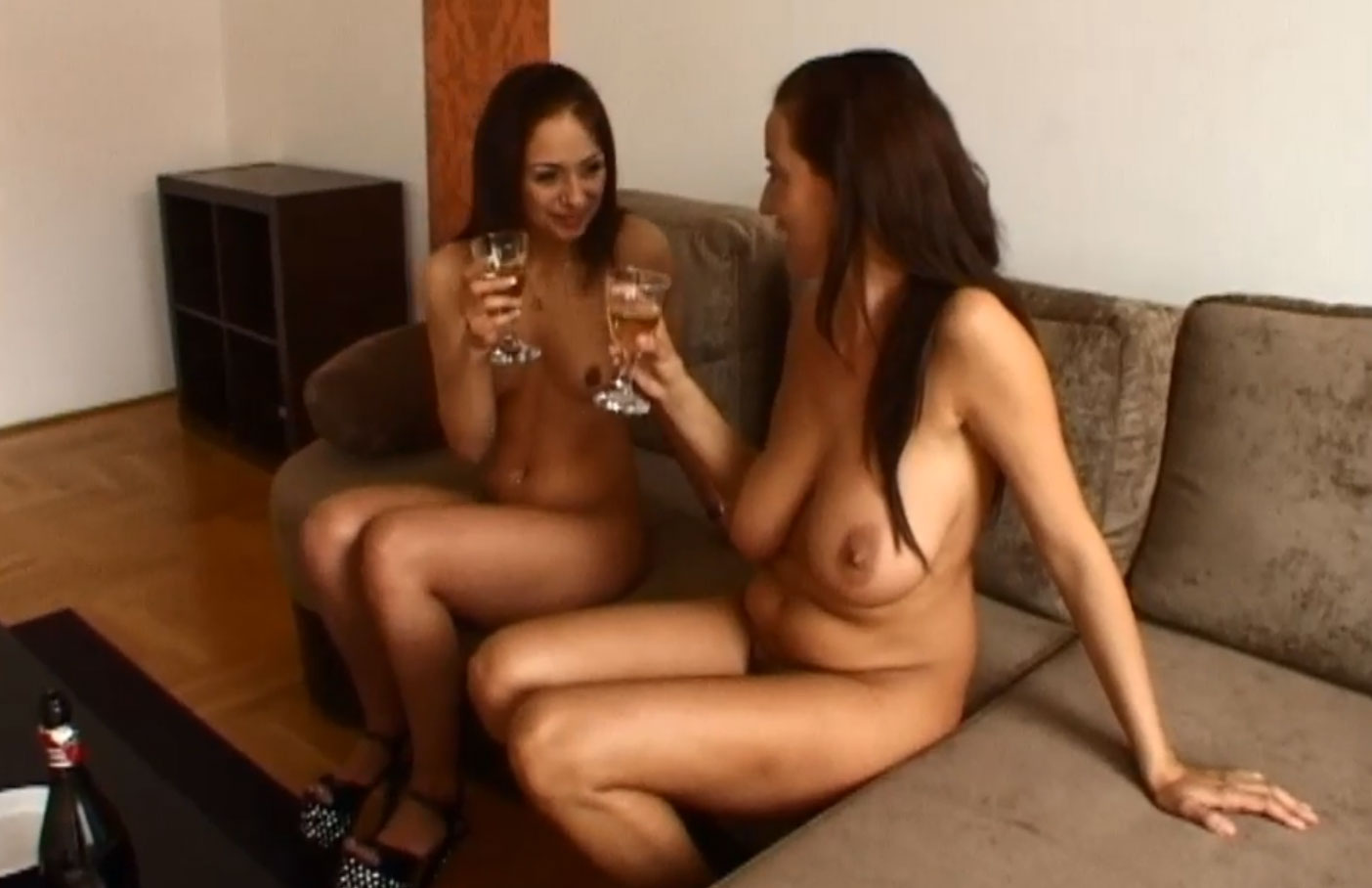 Two Naked friends drinking champagne together